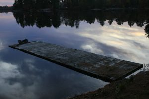 A dock seems to float on clouds, as well as on the lake.